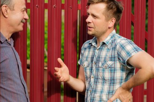two people having a conversation about their shared fence